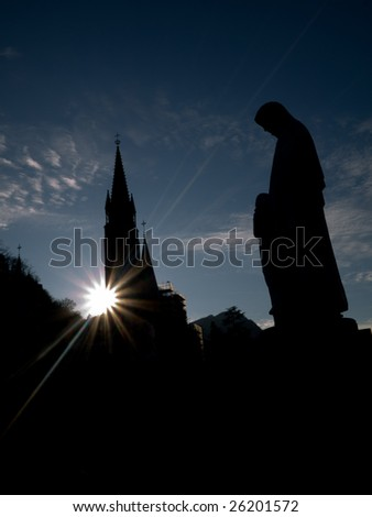 Silhouette of the Basilica of the Immaculate Conception in Lourdes with statue of the virgin Mary