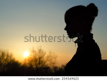 Silhouette of the beautiful girl in the nature at summer sunset.