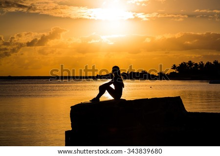 Silhouette of the beautiful girl sitting on the coast watching sunset or sunrise
