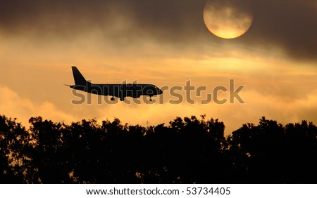 Silhouette of the big plane landing on a sunrise background.