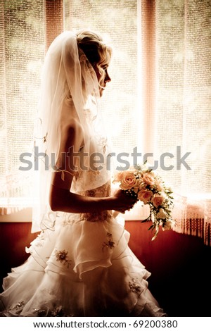 silhouette of the bride weared in dress and veil with a bouquet - stock photo