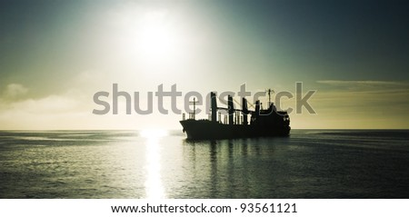 Silhouette of the cargo ship over the sunrise