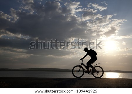 silhouette of the cyclist on road bike at sunset #109441925