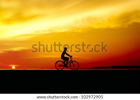 silhouette of the cyclist riding at sunset