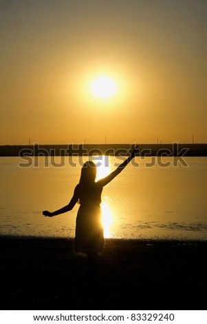 Silhouette of the dancing girl with sunset on the background