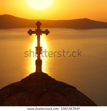 Silhouette of the dome with cross of a Greek orthodox church in Thira in Santorini at sundown, Greece