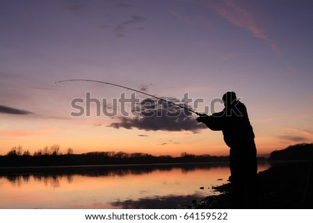 Silhouette of the fisher on a background of an evening dawn