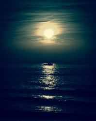Silhouette of the fisherman or leisure boat sailing toward the moon. Dark sky and clouds. Moonwalk. Reflection in water. Beautiful seascape in the night. Harmony with nature idea. Mystery background.