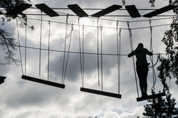 Silhouette of the girl on Dangerous ropeway with tether in rope park