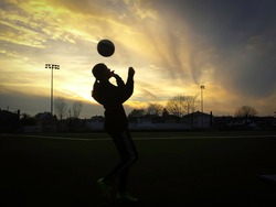 Silhouette of the Girl playing soccer  at Sunset with beautiful clouds in the background.
