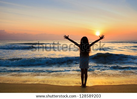 Silhouette of the girl standing at the beach during beautiful sunset.