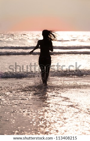 Silhouette of the girl with a flying hair, running across the ocean at sunset