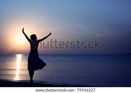Silhouette of the happy woman in summer dress standing at the beach during sunset. Natural light and colors
