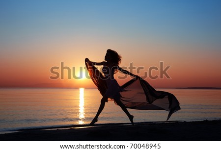 Silhouette of the happy woman with fiber dancing and jumping at the sunset beach