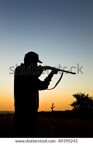 Silhouette of the hunter on a background of a morning dawn