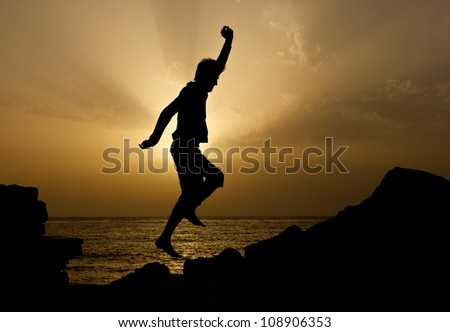 Silhouette of the jumping man on sunset sun. Jumping man near the sea. Happy man. Silhouette of man jumping on sunset. Unknown man on sunset. Sunset. Man on holidays