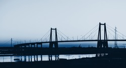 Silhouette of the large suspension concrete bridge near Figueira da Foz, Portugal. Color of the year 2020 classic blue toned
