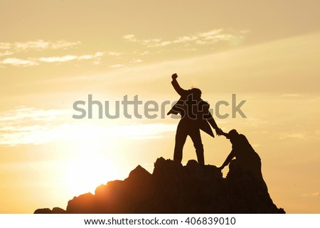 Silhouette of the man Bring hand up a friend to top the peak of mountain on sunrise sky , Business success goal together, Conceptual design. #406839010