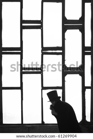 Silhouette of the Man in the black coat and hat in the dark interior near the meshedwindow. Monochrome photo