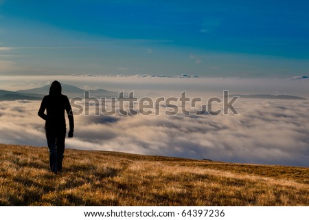 silhouette of the man walking above the clouds