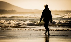 Silhouette of the man, walking on the ocean beach