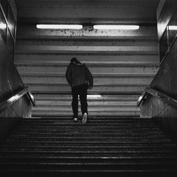 silhouette of the man walking on the stairs in the tunnel leading to train station