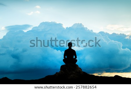 Silhouette of the meditating person against an approaching thunder-storm #257882654