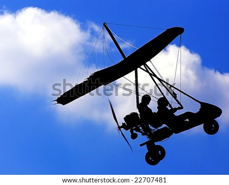 Silhouette of the Microlight Glider in the Blue Sky