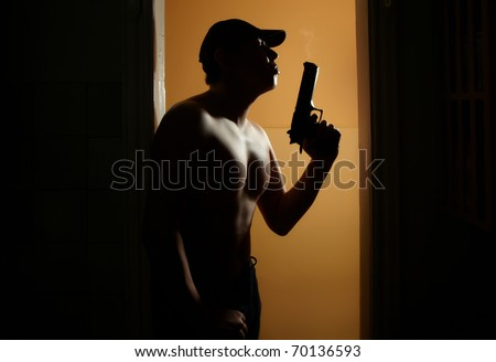 Silhouette of the muscular man with fuming gun in the dark interior with orange walls