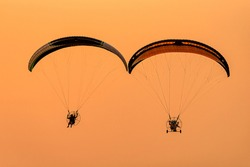 Silhouette of the Paramotor gliding and flying In the air through soft sunlight sky. Paramotor it is extreme sport