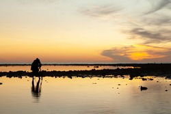 Silhouette of the photographer looking to the viewfinder on camera to capture the sunset in the evening at Pakarang beach, Phang Nga, Thailand