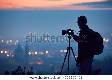 Silhouette of the photographer with tripod. Young man taking photo with his camera in the night city. Prague, Czech Republic.