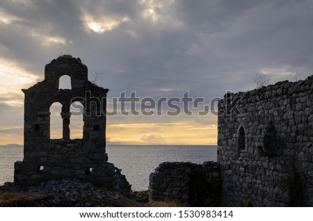 Silhouette of the remains of an old stone church with the sea on a cloudy day in Mani Greece