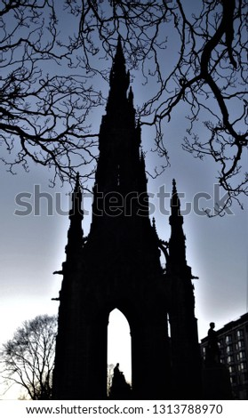 Silhouette of the Scott Monument, with on the top of it the beautiful ramification of some branches. Pic taken  in the blue hour, in the Princes Street (Edinburgh, Scotland).