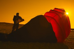 Silhouette of the skydiver next to the partially filled canopy of the parachute after landing on the field, a snapshot in warm tones. Orange filter. Parachute jumps.