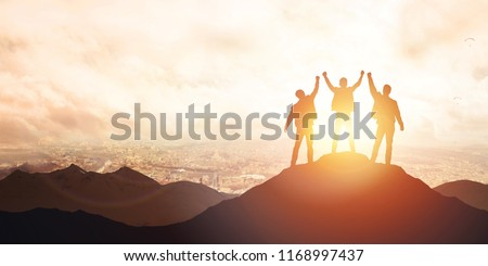 Silhouette of the team on the mountain against the backdrop of the city. Leadership Concept #1168997437