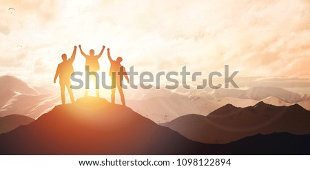 Silhouette of the team on the mountain. Leadership Concept #1098122894