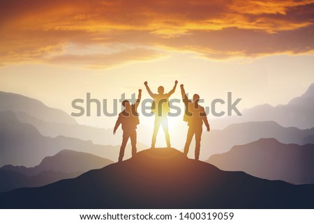 Silhouette of the team on the mountain. Leadership Concept #1400319059