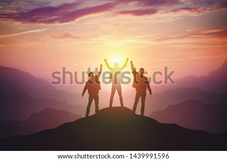 Silhouette of the team on the mountain. Leadership Concept