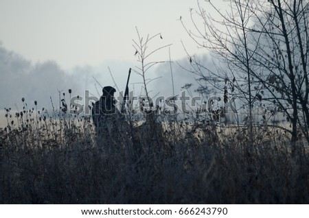 Stock Photo Silhouette of the two hunters at sunrise. Hunter man and boy during hunting period in search of wildfowl or game. Autumn hunting season. Grandfather teaches his grandson the hunting craft