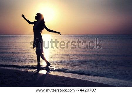 Silhouette of the woman at the beach during sunset. Natural light and colors