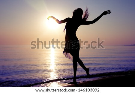 Silhouette of the woman dancing at the beach during beautiful sunrise. Natural light and darkness