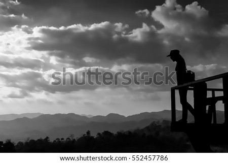 Silhouette of the woman standing alone at the deck during sunset, Thailand countryside. Black and white background.
