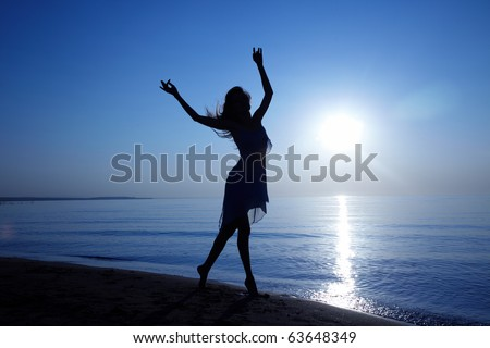 Silhouette of the woman with long hairs dancing at the beach during sunset. Artistic colors added