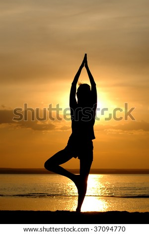Silhouette of the women meditate on sundown