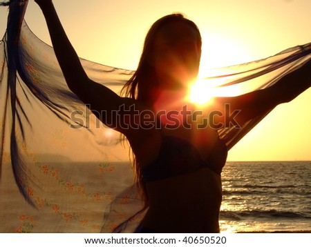 Silhouette of the young woman against a sunset