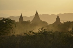 Silhouette of Three Ancient Buddhist Temples Along dusty road in Bagan, Myanmar