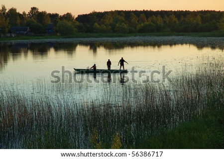 Silhouette of three fishermen in a small boat on a lake at sunset
