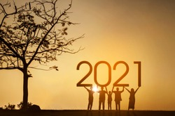 Silhouette of three generations family holding 2021 numbers while standing near a tree at the park. Shot at sunrise time