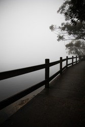 Silhouette of timber fence railing looking out to mist fog simple minimal